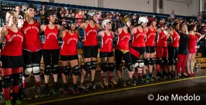 The Pissahs watch the final jams of their playoff bout together, a moment that co-captain Neurotic Tendency said showed the solidarity that makes her love her team. Photo by Joe Medolo.